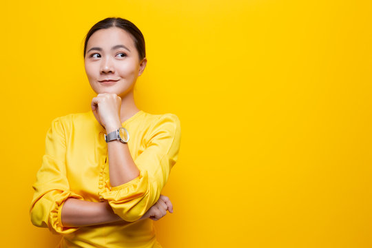 Happy woman thinking and standing isolated over yellow background