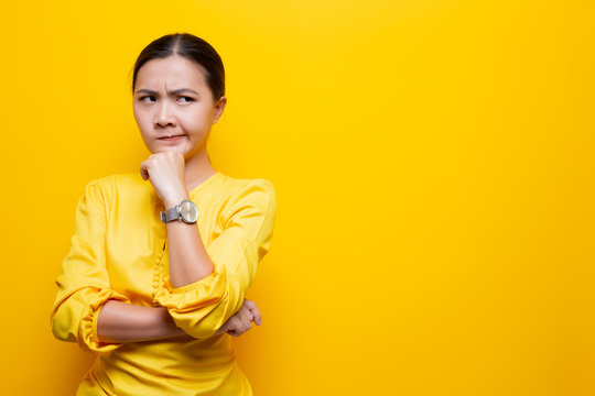 Woman feel confused isolated over yellow background