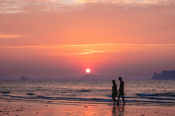 Silhouettes of people on a background of a sunset sea landscape