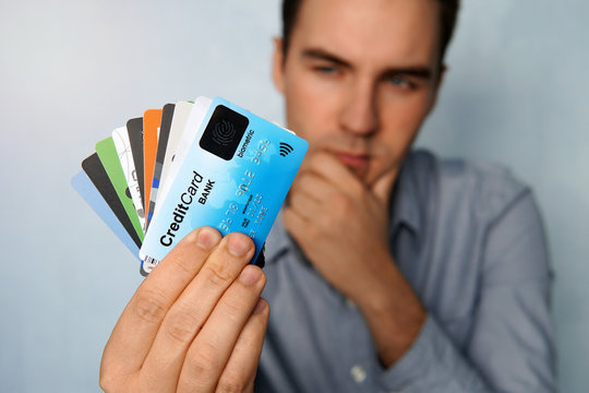 The young man is holding a stop of credit and debit cards in a pensive pose. The guy chooses a card to pay. businessman holds a large stack of credit cards in his hand and looks at them