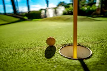 Mini Golf yellow ball on green grass at sunset