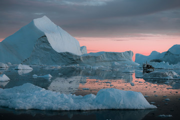 Small boat in front of a floating Iceberg in Greenland during sunset