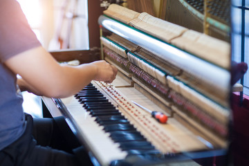 Musician or technician tuning piano using lever and tools