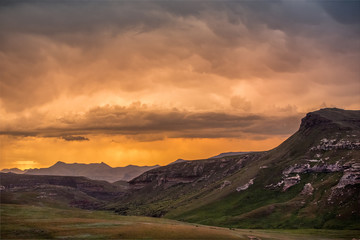 Cliffs and mountains under dramatic colorful storm clouds at sunset over the Drakensberg mountains surrounding the Amphitheatre, seen from Golden Gate Highlands National Park, South Africa