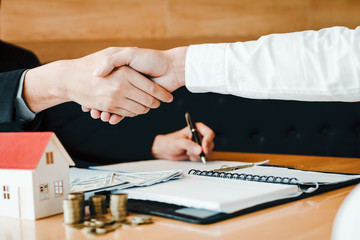 Home sales agents and buyers work on signing new homes and shaking hands.
