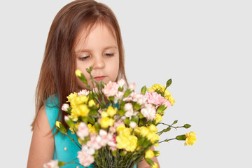 Sideways shot of cute small girl with long hair, enjoys pleasant odour from flowers, dressed in fashionable blue dress, isolated over white background with copy space for your promotion or text