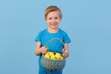 Child and Easter. Smiling blond boy, 6 years old, holding yellow eggs in a basket and small chickens. Blue studio background. Indoor waist up portrait. Male in front. Facing camera.