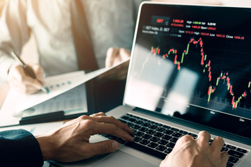 Investors are using laptops entering investment websites stocks market and partners are taking notes and analyzing performance data.