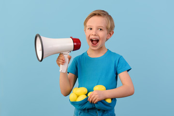 Child and Easter. Smiling blond boy, 6 years old, holds a megaphone and yellow eggs in his hand. Easter time. Waist up portrait. Blue studio background.