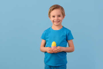 Child and Easter. Smiling blond boy, 6 years old, is holding a yellow egg in his hand. Easter time. Waist up portrait. Blue studio background.