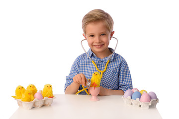 The child and Easter eggs. He examines eggs with a stethoscope. Isolated on white.