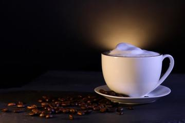 Tasse mit Kaffee mit Milchschaum und Kaffeebohnen als Dekoration