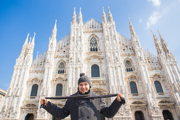 Italy, excursion and travel concept - funny guy taking selfie in front of cathedral Duomo in Milan