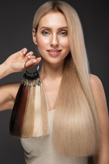 Beautiful blond girl with a perfectly smooth hair, classic make-up with a palette for hair extensions in the hands. Beauty face.