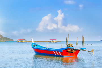 Traditional asian fishing boat anchored against blue sky with clouds on a sunny morning. Copy space