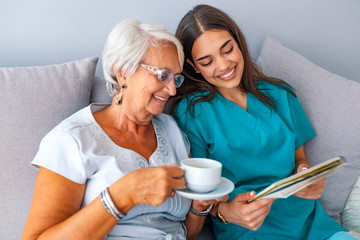 Young nurse spending time with happy elder patient in nursing home.
