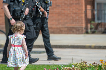 little girl walks in front of armed police patrol in tourist town respond to terrorist critical threat level