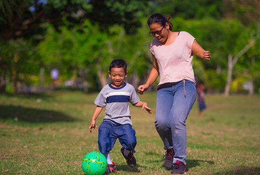 happy Asian Indonesian mother playing football with little 5 years old son running together excited laughing having fun in soccer fan child and healthy lifestyle education