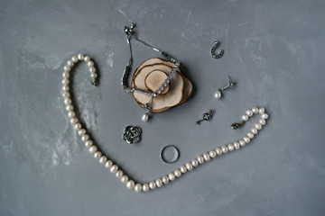 Silver jewelry on a gray background with a string of pearls