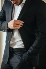 A man in a black suit and white shirt poses indoors for advertising men's clothing. Shooting for men's clothing store