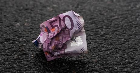 Zerknitterter Fünfhundert Euroschein auf Asphaltstraße