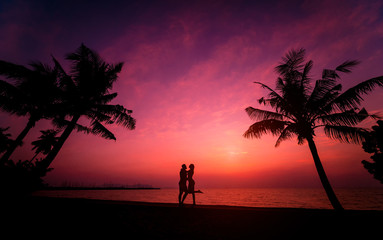 Silhouette of couple on tropical beach during sunset on background of palms and sea