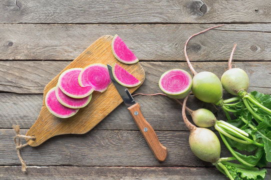 Sliced watermelon radish (chinese daikon) with green leaves on wooden table. Top view.