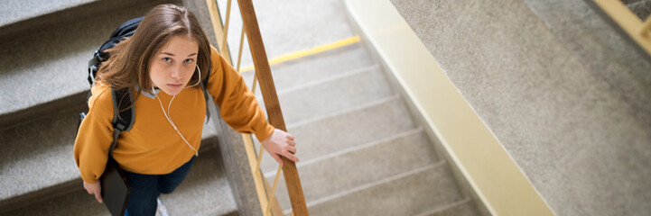 Young depressed lonely female college student walking down the stairs at her school, looking up at the camera. Education, Bullying, Depression concept.