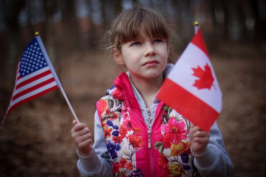 Little girl holding canadian and american flag