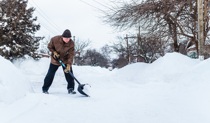 Man with a shovel cleans the track from the snow