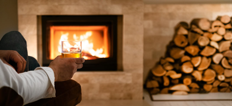 Man sitting at home by the fireplace and drinking a whiskey.