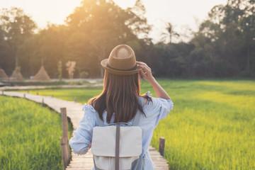 Young woman traveler looking at beautiful green paddy field