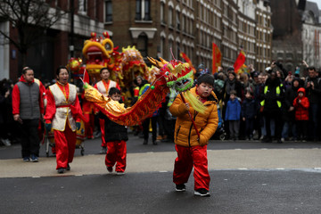 Spectators move a traditional Chinese dragon as they take part in the Chinese Lunar New Year parade through central London