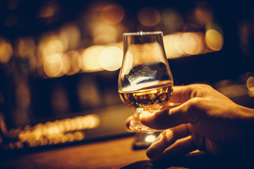 Stores photo Alcool Hand holding a Glencairn single malt whisky glass