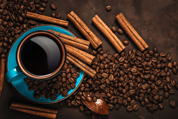 Cup of aromatic black coffee, coffee beans and cinnamon sticks on dark background. Still life.