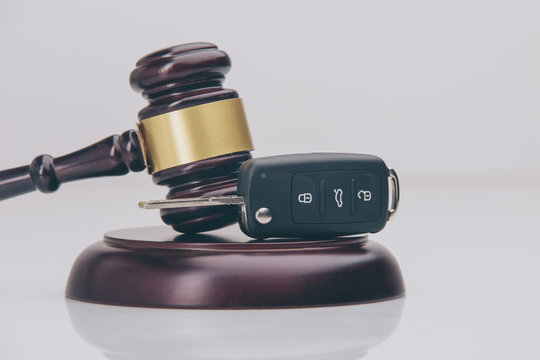 Close-up Of Gavel And Car Key On Sounding Block Against Grey Background