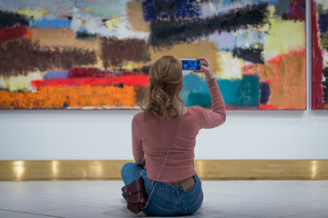 the girl sitting on floor and stares at the picture in the Gallery of modern art