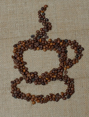 A cup and saucer of coffee beans. Whole bean coffee. Coffee cup on burlap