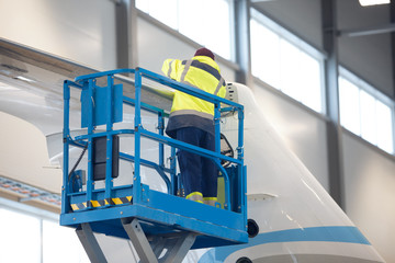 Worker repair airplane while standing on scissor lift