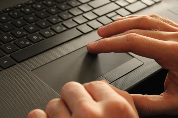 Hand on touchpad of laptop.