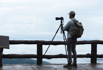 Young man travel photographer taking nature photo of mountain landscape  (Thailand )