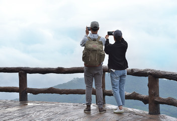 Woman and man tourist using smartphone taking nature photo of mountain landscape (Thailand)