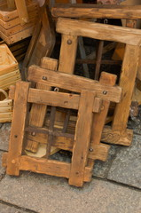 close up of rustic wooden and wrought iron windows, wooden frame and wooden containers resting on the ground
