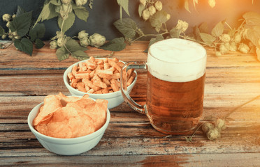 Glass mug of cold fresh golden beer with crackers and chips on w