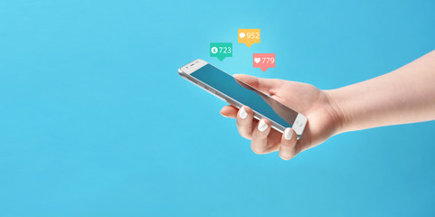 Girl's hand holding smartphone in hand, surrounded with social media notification icons on blue background