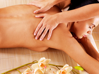 Masseur doing massage on woman back in spa salon