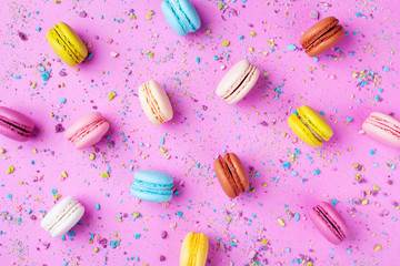 Colorful cake macaron or macaroon on pink background top view. Flat lay style.