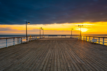 Wooden pier in Jastarnia village on Hel Peninsula at sunset time. Poland.