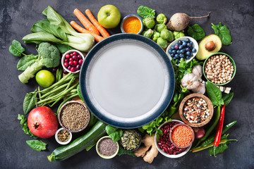 Healthy food selection with fruits, vegetables, seeds, super foods, cereals and the plate in the middle
