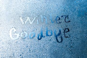 The inscription: goodbye, winter. On a frozen winter window in frosty patterns
